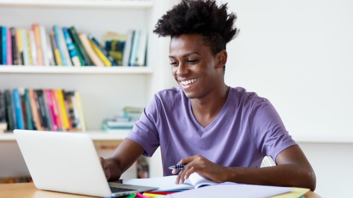 Jovem negro sorrindo ao estudar no computador