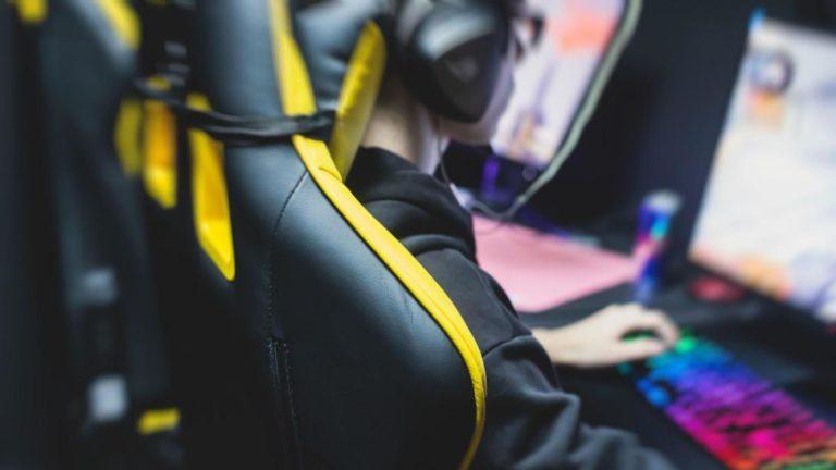 Homem jovem sentado em uma cadeira preta e amarela olhando para a tela de um computador, jogando online