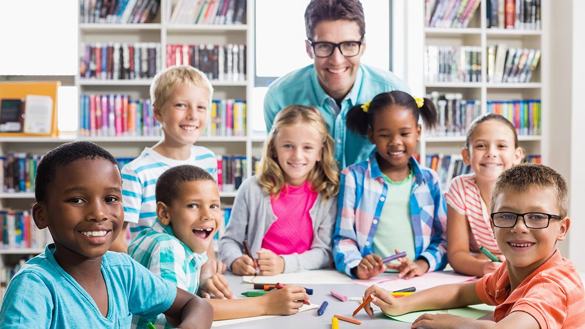 Professor com algumas crianças aprendendo inglês