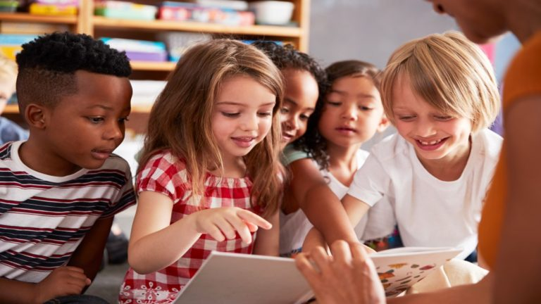 Diversas crianças olhando para um livro que uma mão adulta feminina mostra pra eles