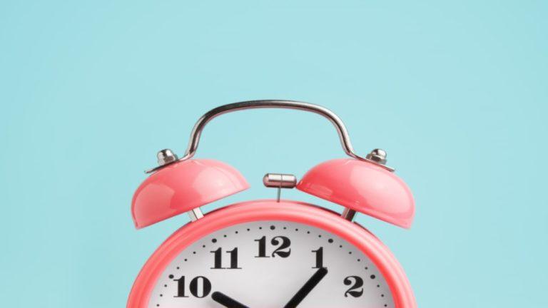 Parte superior de um relógio rosa de ponteiro e fundo azul
