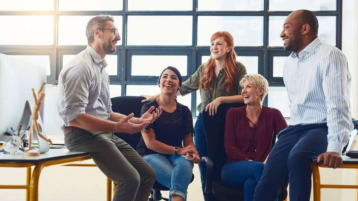 Dois homens e três mulheres em um escritório em conversa descontraída