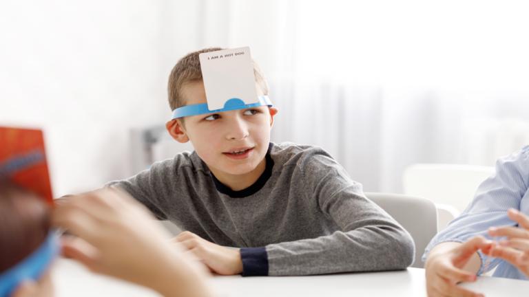 menino branco de camisa cinza com um papel colado em sua testa