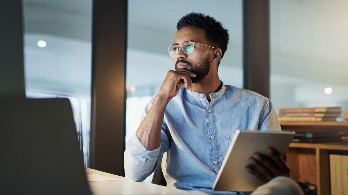 Homem negro olhando para a tela de computador e a avaliando