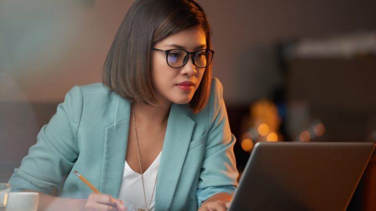 Mulher oriental de óculos e blusa verde olhando a tela de um notebook e fazendo anotações