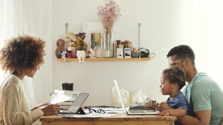Uma mulher sentada em um lado da mesa e olhando o notebook, do outro lado da mesa um homem sentado com uma criança em seu colo, eles também olham para outro notebook a sua frente