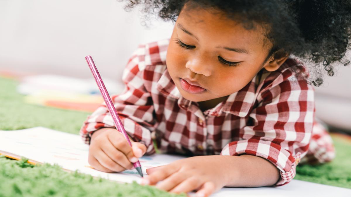 Uma menina negra que veste uma camisa xadrez escrevendo em um papel