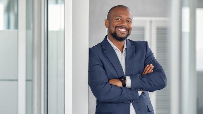 Homem negro sorrindo de terno azul encostado em uma parede