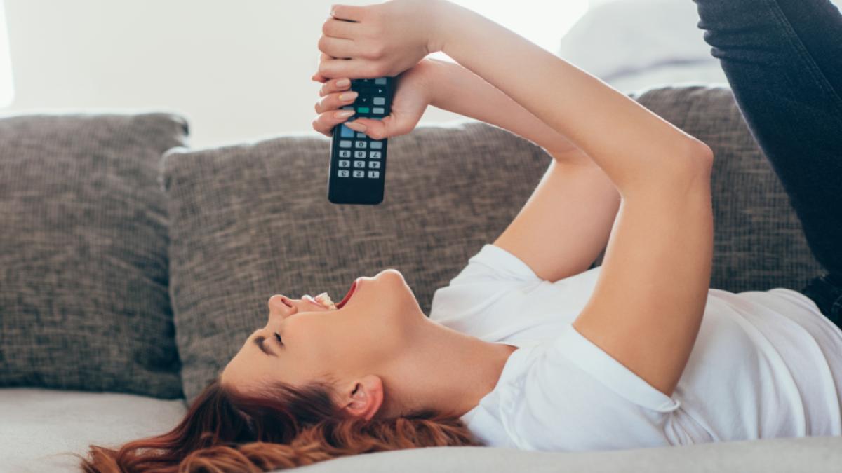 Mulher deitada no sofá e usando o controle da TV como um microfone de brincadeira