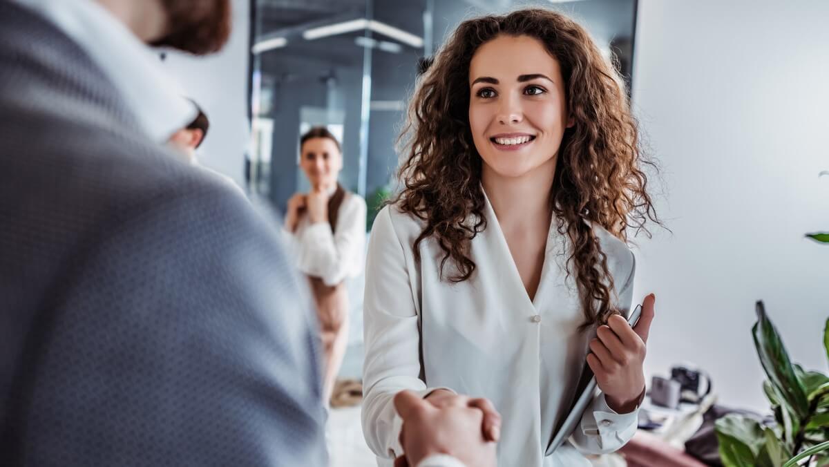 Mulher de cabelo castanho e camisa branca apertando a mão de um homem que está de costas, simbolizando um novo negócio fechado
