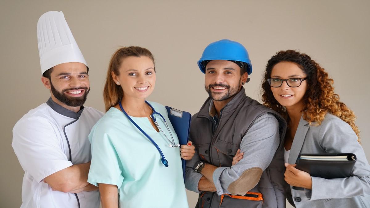Um homem vestido de cozinheiro, uma mulher vestida de enfermeira, outro homem de construtor e uma mulher de professora