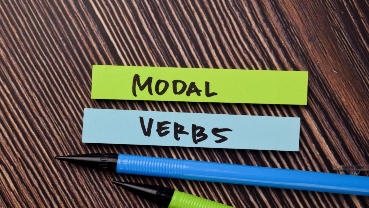 """Um pequeno papel verde escrito """"modal"""" e outro azul do mesmo tamanho escrito """"verbs"""""""