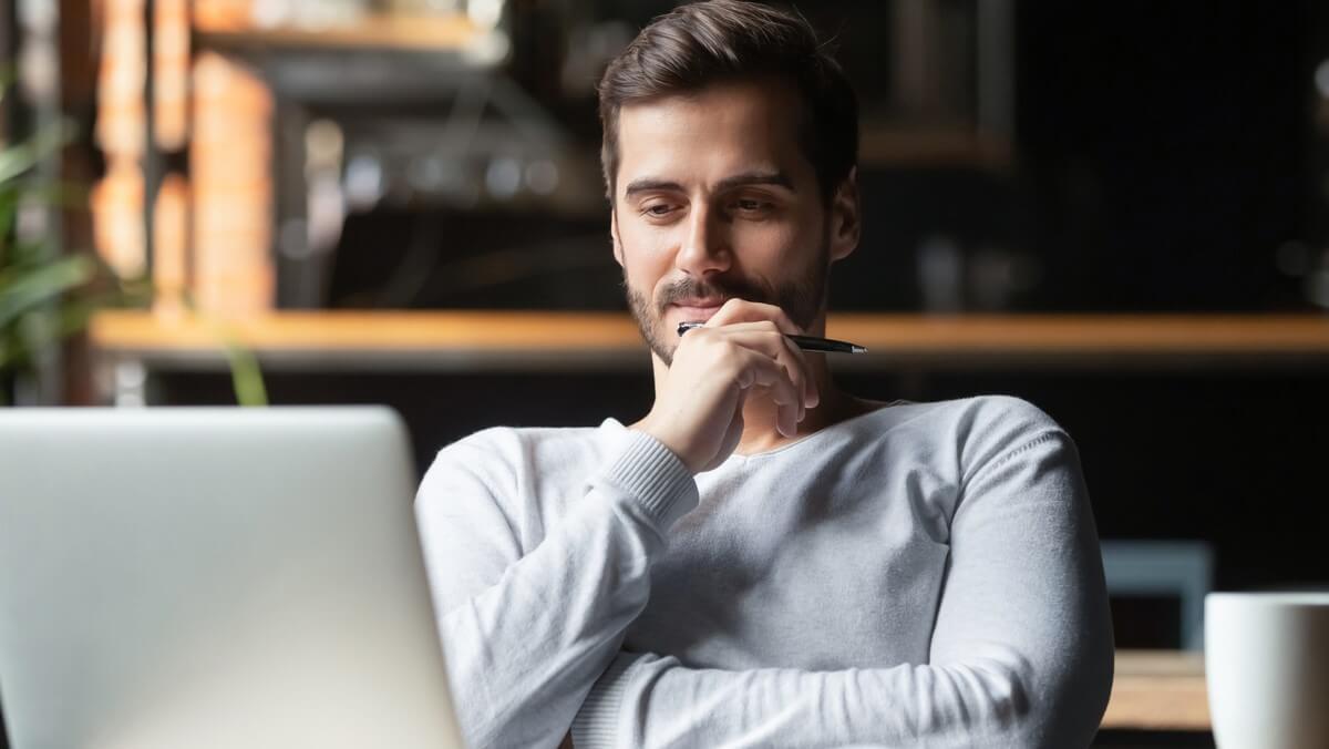 Homem branco de camiseta cinza sentado, com a mão no rosto e olhando a tela de um notebook