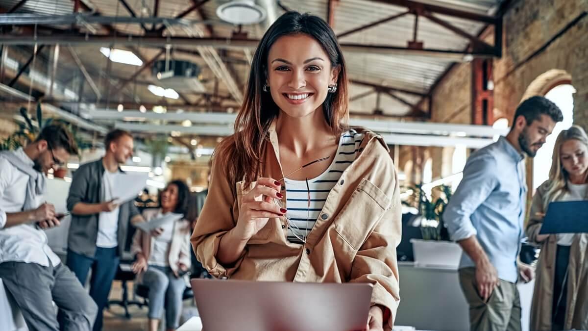 Mulher encostada em uma mesa com o computador na mão e olhando pra frente, ao fundo há outras pessoas conversando entre elas