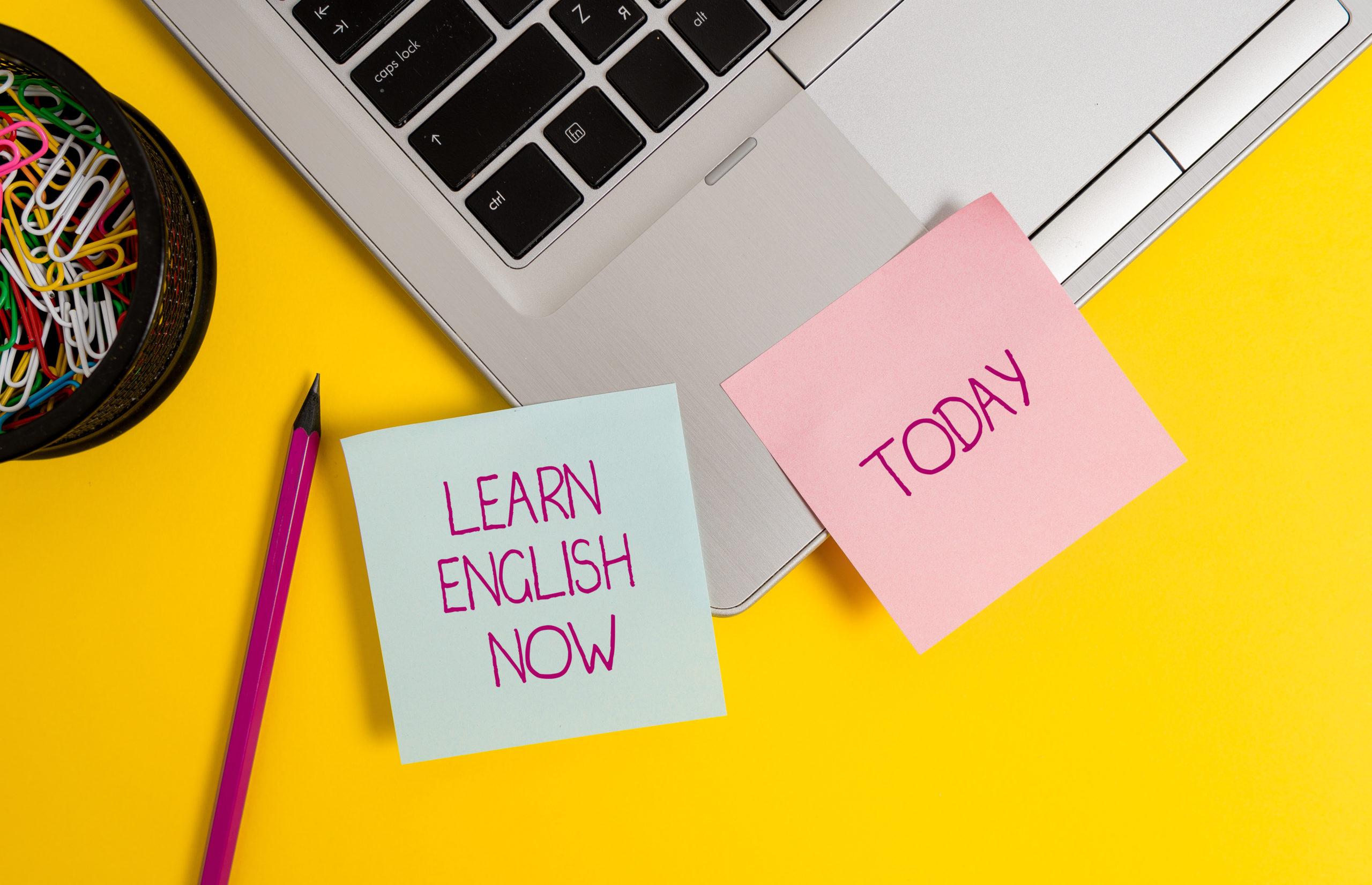 """teclado de um notebook e abaixo dois recados, um escrito """"learn english now"""" e outro escrito """"today"""""""