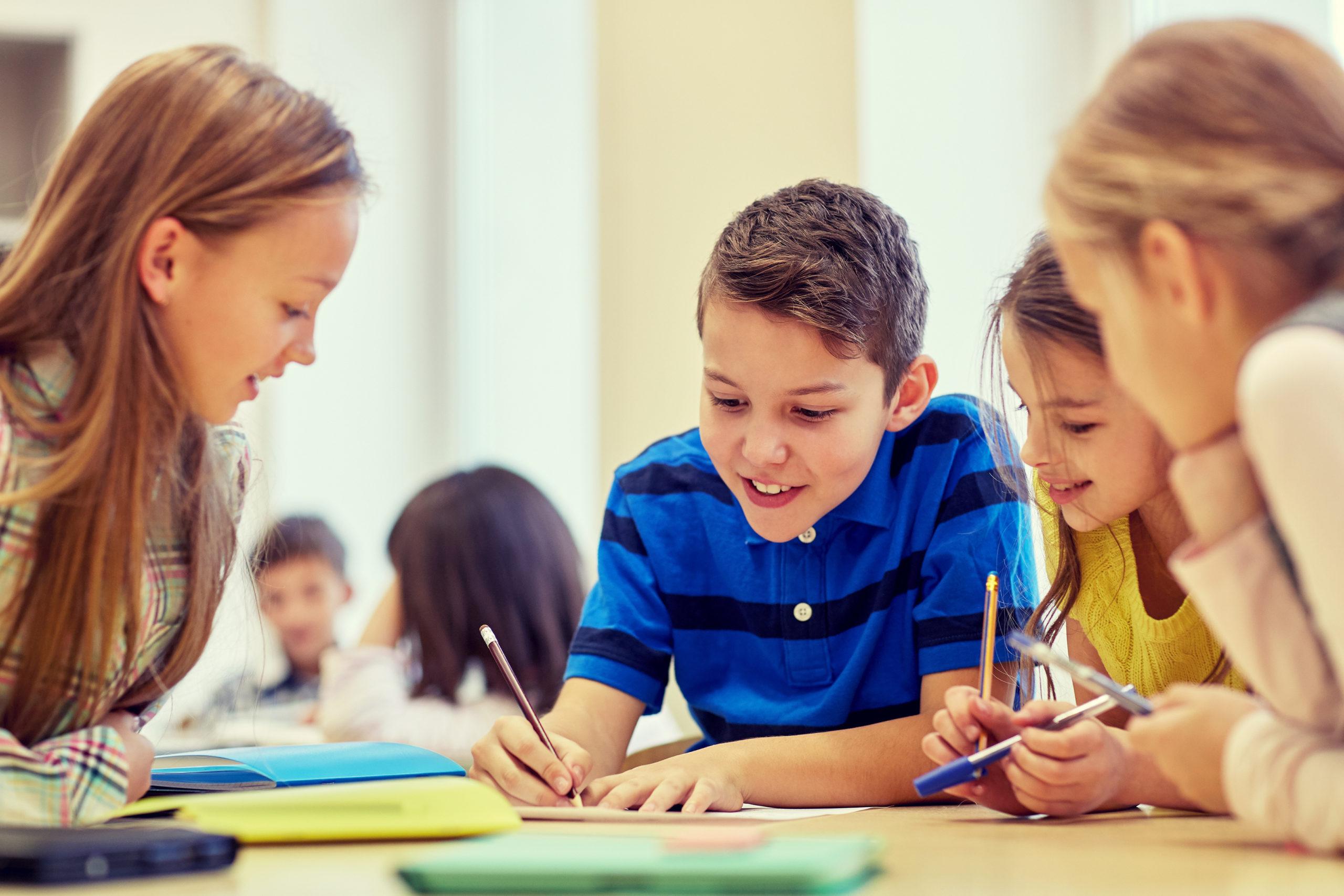 Grupo de crianças sentada ao redor de uma mesa fazendo uma atividade em grupo