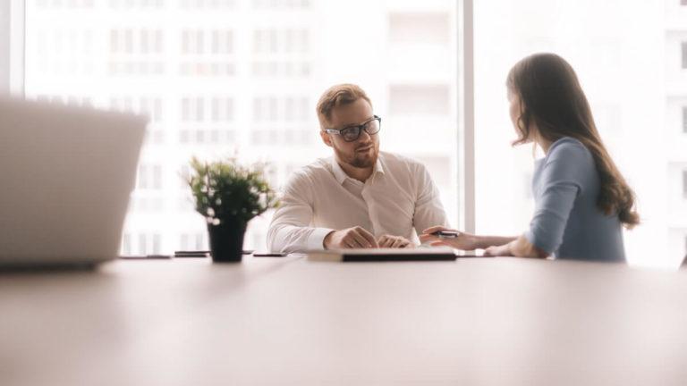 Mulher de camisa azul e homem de camisa branca conversando em uma mesa de reunião