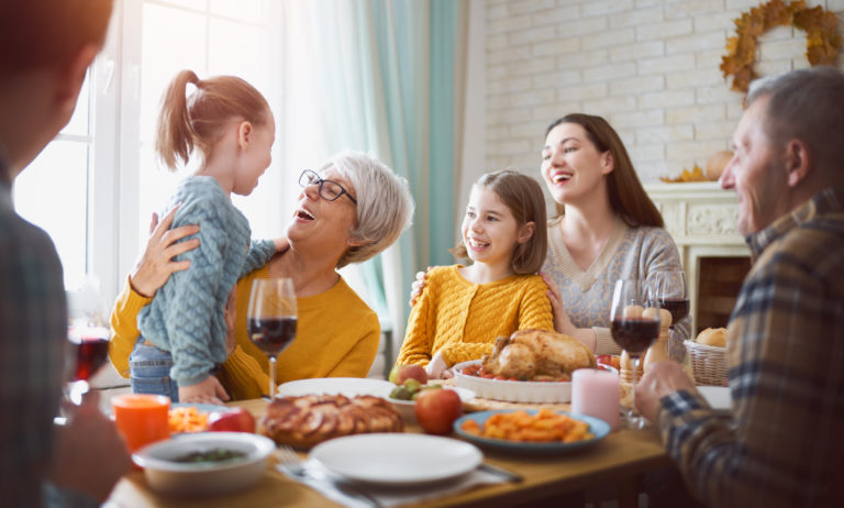 Uma mulher jovem, uma idosa e duas meninas ao redor de uma mesa de jantar sorrindo