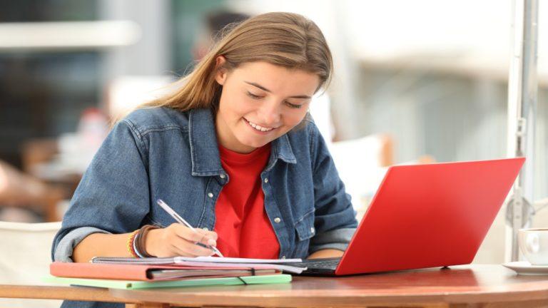 Garota sentada numa mesa com alguns livros e um notebook