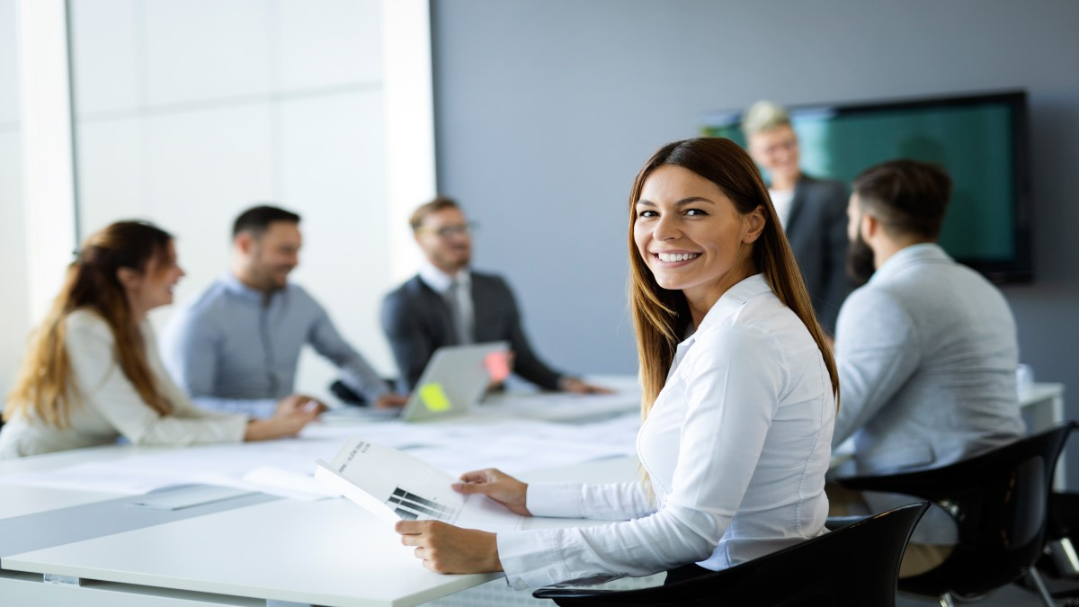 Sala de reunião com algumas pessoas e uma mulher com camisa e cabelo castanho e longo está olhando para a tela