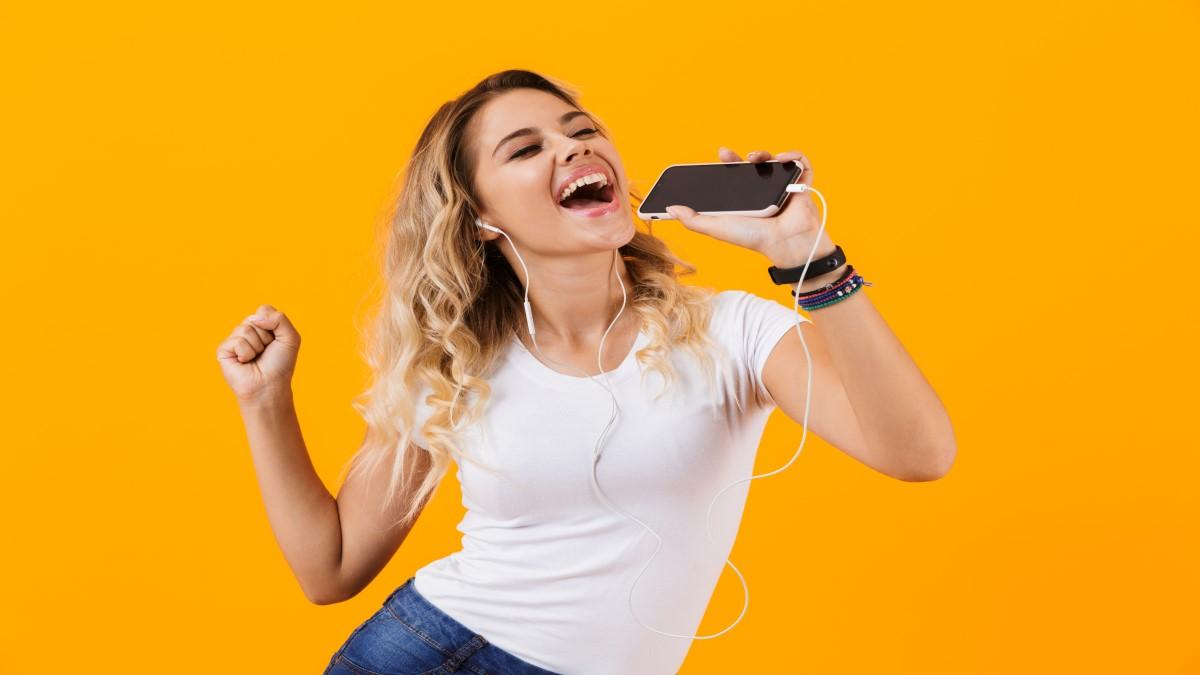 Mulher loira com blusa branca segurando um controle remoto e simulando cantar, o fundo da imagem é todo laranja