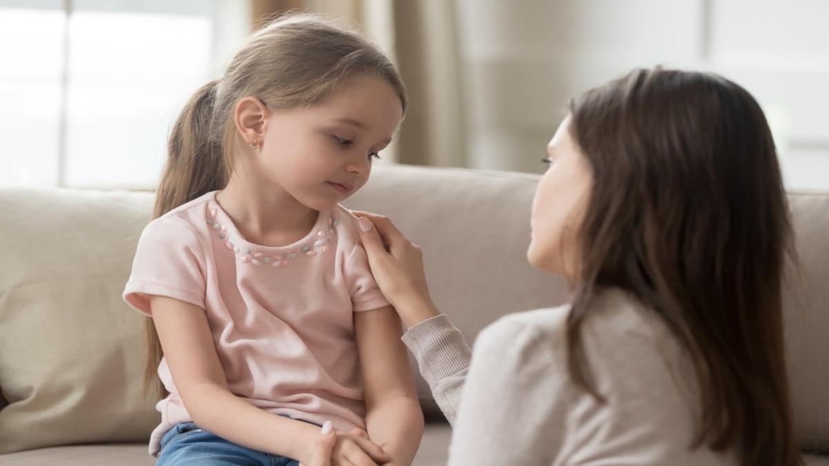 Menina sentada em um sofá e sua mãe abaixada na frente dela