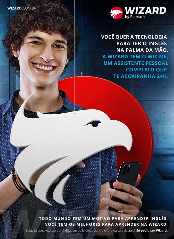 Homem branco com cabelo cacheado sorrindo e segurando o celular com a mão direita entre o logo da Wizard