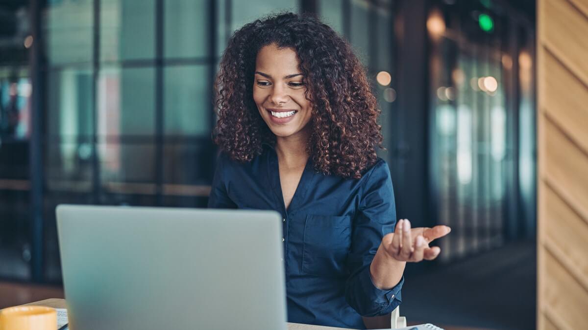 Mulher de cabelo cacheado olhando para a tela de um notebook e sorrindo