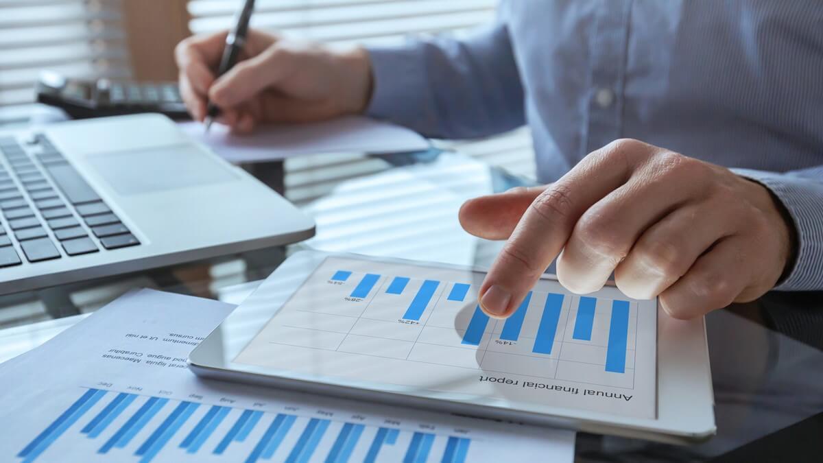 Um par de mãos masculinas mexendo em um tablet com alguns gráficos
