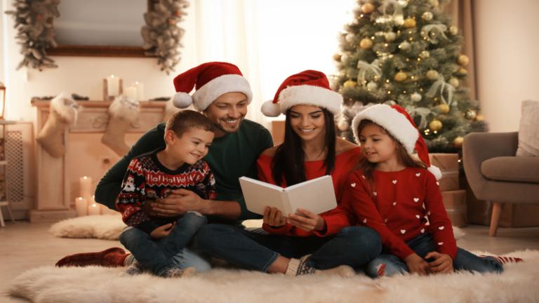 Um homem e uma mulher lendo histórias para duas crianças. Todos estão vestindo gorro de Papai Noel e ao fundo há decoração natalina.