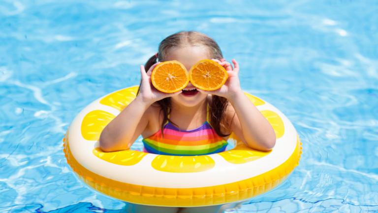 Garota de maiô colorido na piscina, com uma boia amarela ao redor do seu tronco e segurando uma fatia de laranja a frente de cada um dos olhos