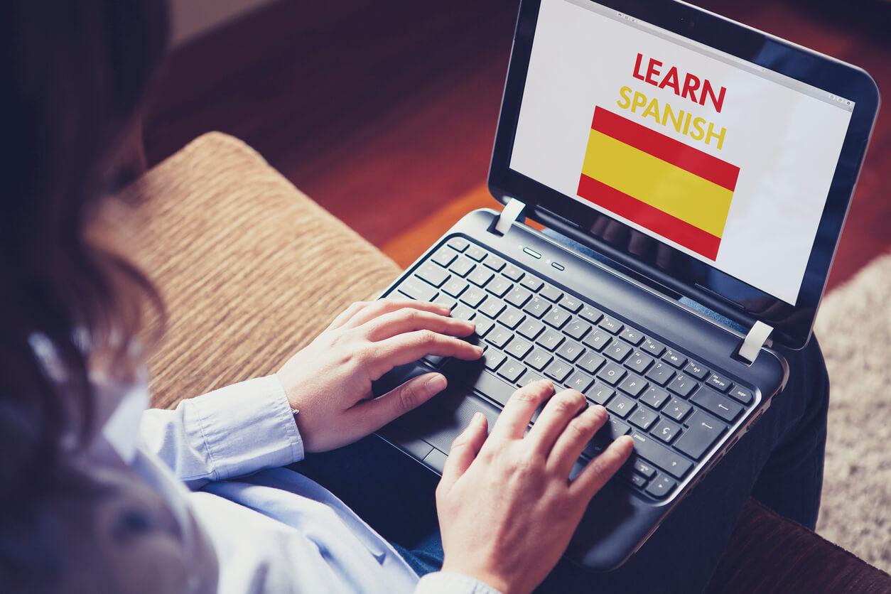 """Mulher com um laptop no colo e as mãos no teclado dele. Na tela, há uma bandeira com as cores da Espanha e escrito a frase """"hablas español"""""""