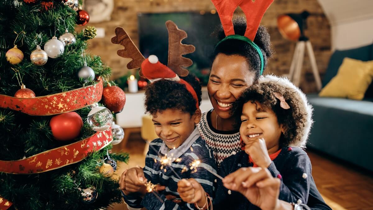 Uma mulher e duas crianças negras montando uma árvore de natal. Todos usam adornos natalinos na cabeça