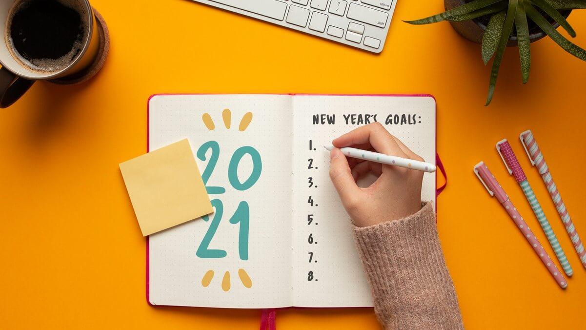 """Caderno aberto em uma mesa amarela e escrito """"metas para 2021"""". Uma mão feminina escreve nele."""
