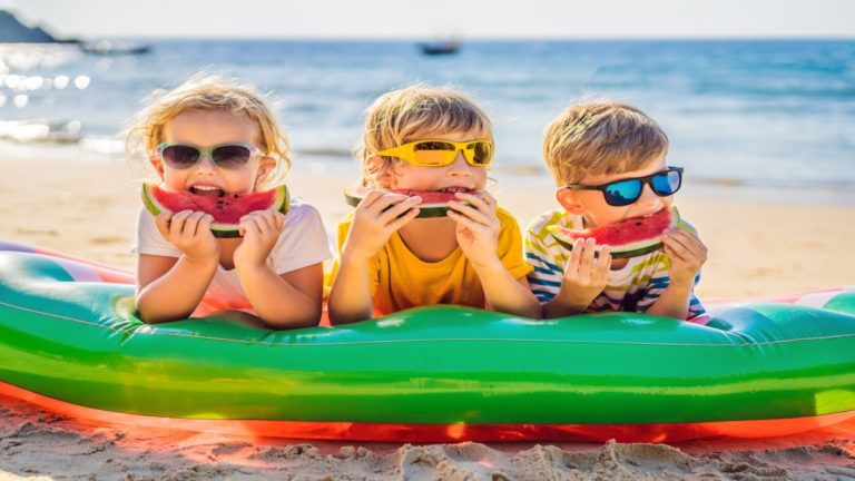 Três crianças apoiadas em uma boia na areia da praia comendo cada uma um pedaço de melancia