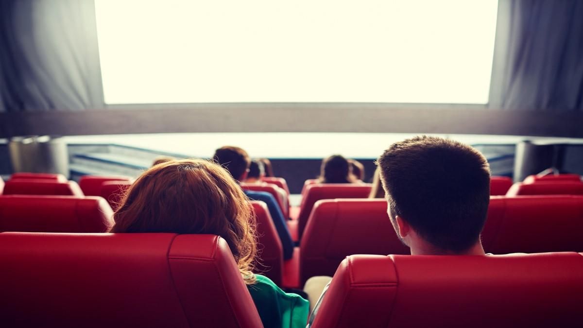 Duas pessoas sentadas em poltronas e olhando para a tela de cinema