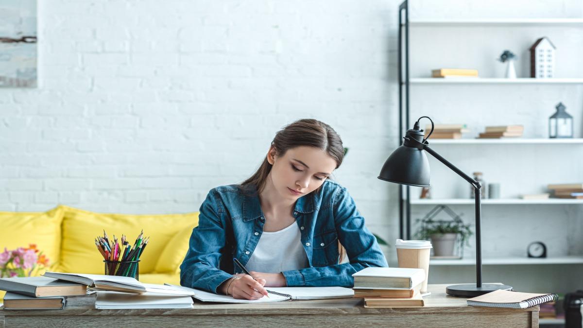 Mulher escrevendo em um caderno com livros sob a mesa