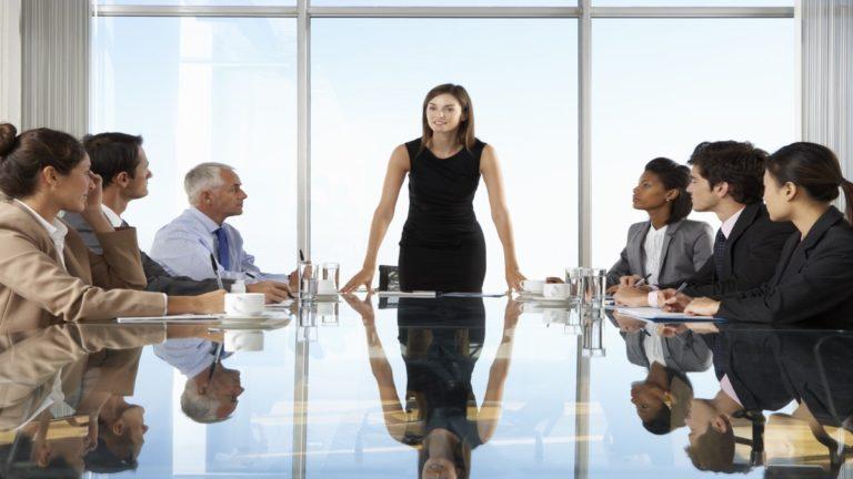 Executiva em reunião com colaboradores em ambiente corporativo