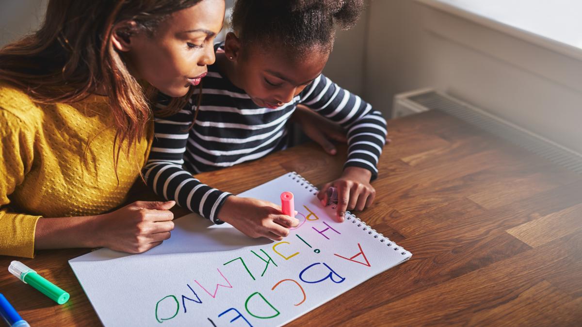 Menina escrevendo letras do alfabeto em um papel ao lado da mãe