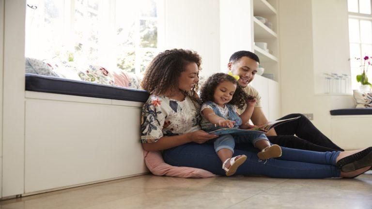 Pais sentados no chão com filha no colo lendo um livro para ela