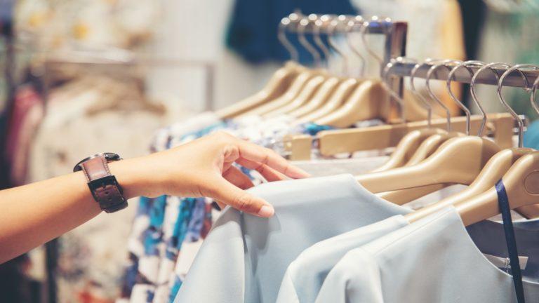Mão selecionando roupas em uma loja