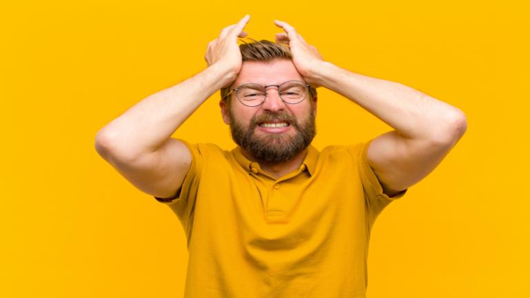 Homem camiseta amarela com as mãos na cabeça e expressão de preocupada