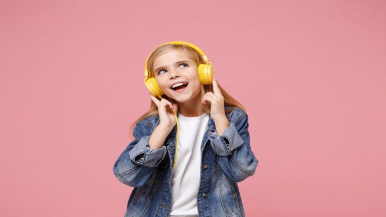 criança alegre escutando música em fone de ouvido
