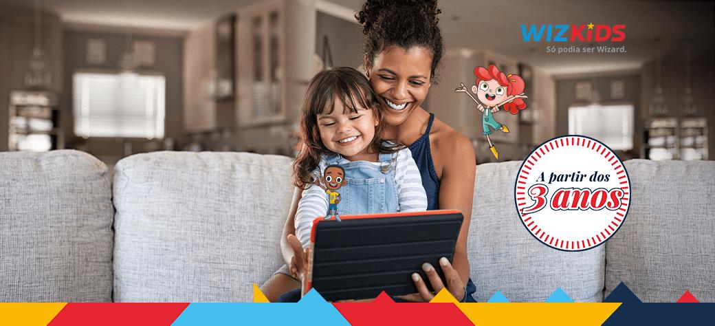 Mãe e filha sorrindo com o notebook em mãos estudando inglês na WizKids - Aulas para crianças a partir dos 3 anos