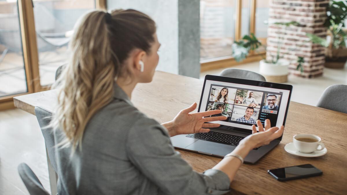 mulher usando fones de ouvido com seu notebook sobre a mesa em uma vídeo chamado com seus companheiros de trabalho