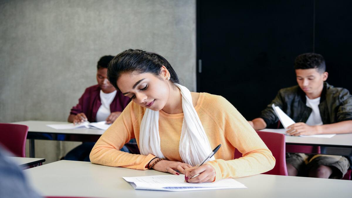 alunos fazendo prova escrita em sala de aula
