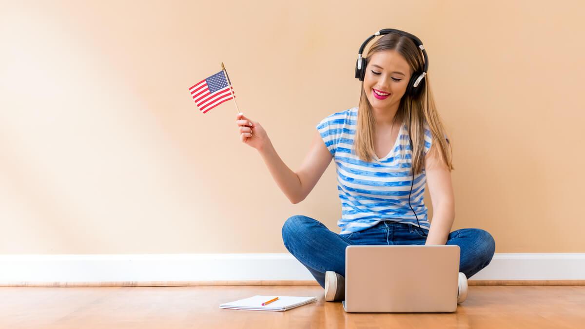 menina sentada ao chão com fones de ouvindo, usando um notebook e segurando uma pequena bandeira dos Estados Unidos da América com a mão levantada ao lado do corpo.