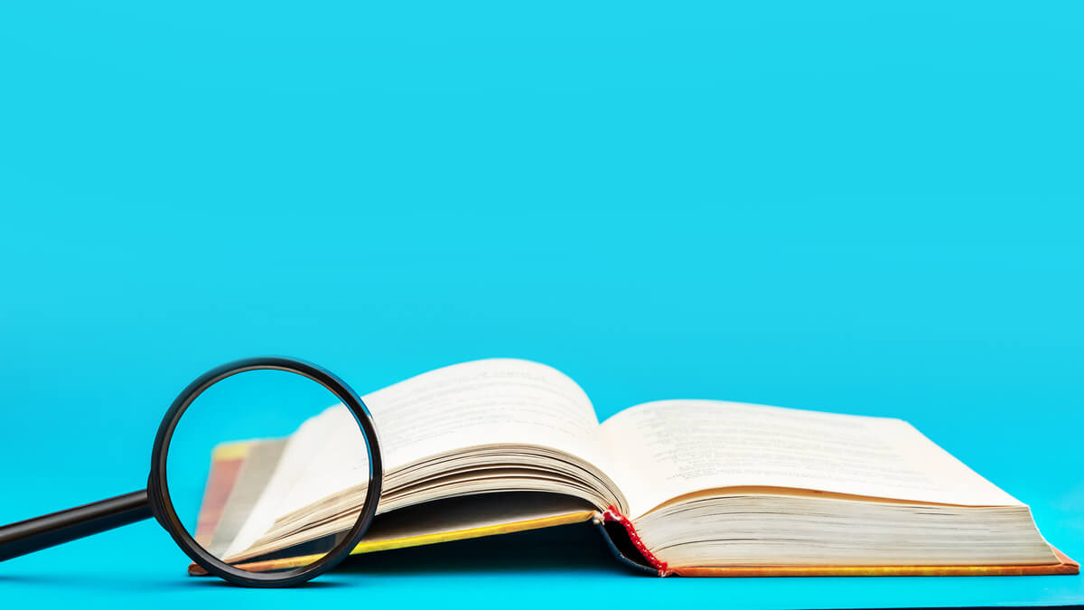 fundo azul, à frente um livro aberto e uma lupa como a examinar o que está escrito em suas páginas.
