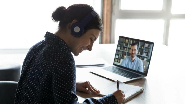 Mulher sorri enquanto escreve em seu caderno e assiste aula online de inglês no seu laptop