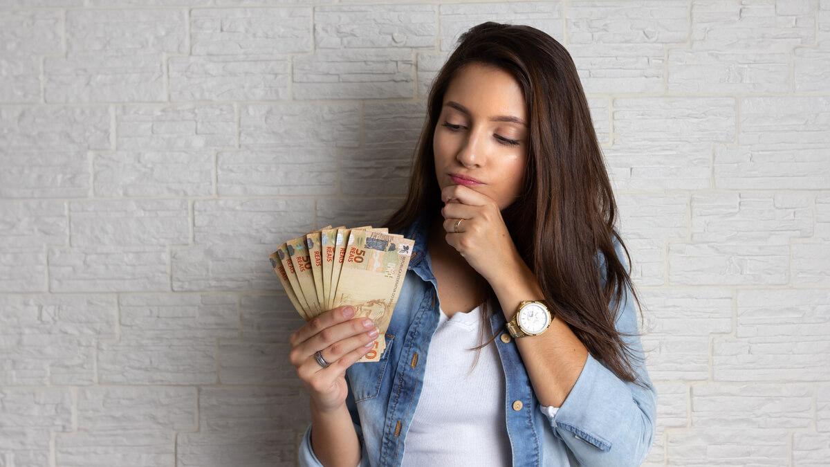 mulher com dinheiro na mão está com cara dúvida